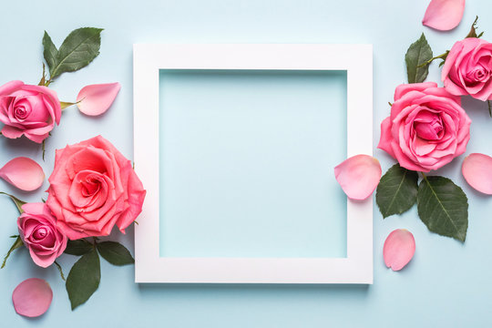 Arrangement of beautiful roses. White paper frame on blue pastel background. Mothers day, Valentines Day, Birthday Greeting card