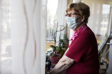 Seniorin mit Mundschutz schaut aus dem Fenster Fotobehang