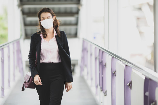 Woman wearing mask waking to work.