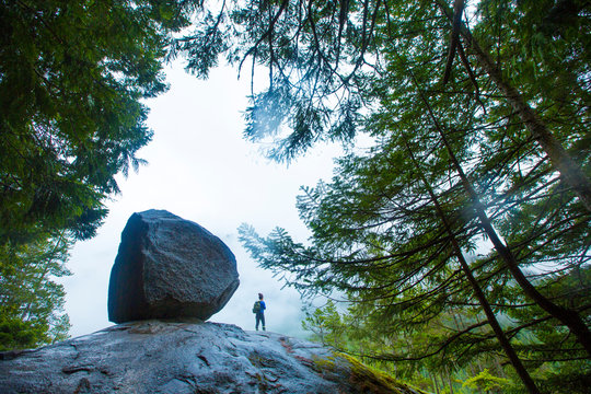 Woman hiker stands next to a huge boulder surrounded by trees of the foggy forest in Squamish on the Stawamus Chief hike.