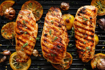 Grilled chicken breasts with thyme, garlic and lemon slices on a grill pan, top view