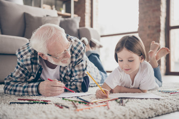Closeup photo of grandpa spending time little granddaughter lying comfy fluffy floor carpet painting colorful pencils best friends stay home quarantine living room indoors