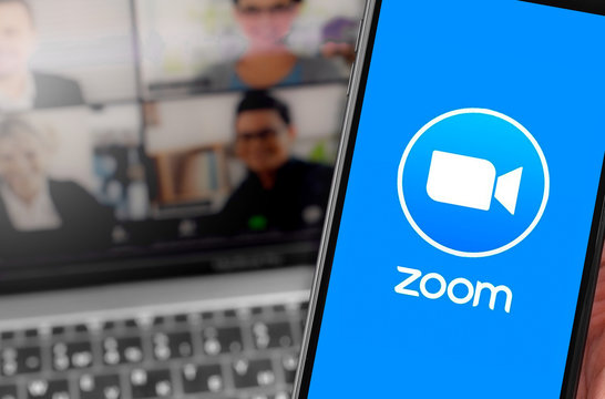 Zoom logo on the screen smartphone with notebook blurred background closeup. Zoom Video Communications is a company that provides remote conferencing services. Moscow, Russia - April 1, 2020