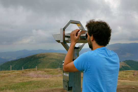 Teenage boy looking through a telescope on top of the Grand Ballon des Vosges, France