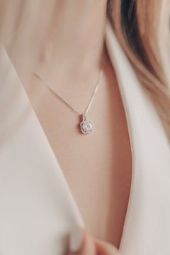 Woman wearing elegant pendant necklace with diamond on close-up