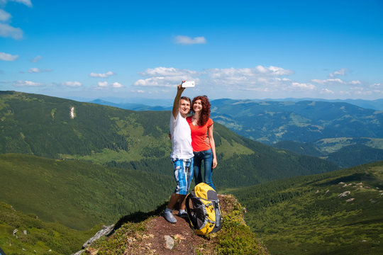 Happy couple hugging in the top of mountain and do selfie photo.