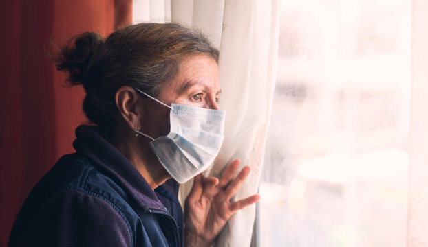 Coronavirus. Sick grandma of corona virus looking through the window and wearing mask protection and recovery from the illness in home. Quarantine.