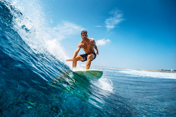 Wall Mural - Young athletic surfer rides the wave in tropics with splashes. Jailbreaks surf spot in Maldives