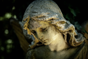 Fotomurales - Beautiful sad angel. Fragment of ancient stone statue with a sweet expression that looks down as symbol of unspeakable sadness and death.