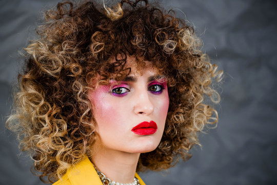 Portrait of a girl in a yellow jacket and blue jeans with afro hair of the eighties, disco era. Photo in studio on a gray background.