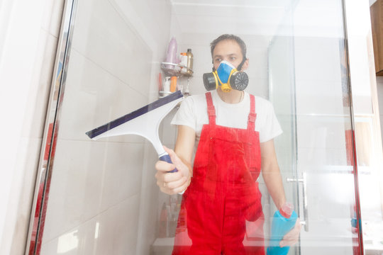 Man cleaning shower cabin.
