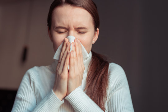 Cough in tissue covering nose and mouth when coughing. European woman sick with flu at home.