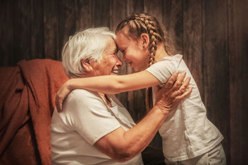 grandmother plays with her granddaughter, depict a plane, hug, time with relatives