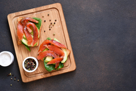 Toast with avocado and salmon on a blackboard on a concrete background.