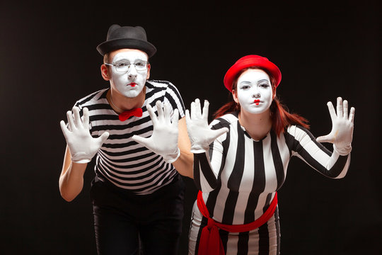 Portrait of man and woman mime artists performing, isolated on black background. Mimes in striped clothes pretending to be behind the glass