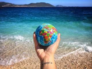 Cropped Image Of Hand Holding Globe At Beach