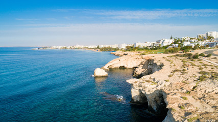 Aerial bird's eye view of coastline landmark 'Love bridge' and sea caves at Cavo Greco, Ayia Napa, Famagusta, Cyprus from above. A tourist attraction cliff rock natural formation arch in Ammochostos.