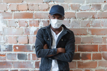 COVID, COVID-19, coronavirus, pandemic Young african black man wearing medical mask is standing in a cap with crossed arms shocked with coronavirus 2019 danger on background of ruined red brick wall Fotobehang
