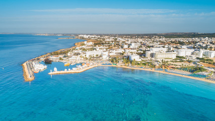 Aerial bird's eye view of Pantachou - Limanaki beach (Kaliva), Ayia Napa, Famagusta, Cyprus. Bay with golden sand, small fishing port, sunbeds, parasols, sea bar restaurants in Agia Napa, from above.
