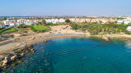 Aerial bird's eye view of Sirena beach in Protaras, Paralimni, Famagusta, Cyprus. The famous Sirina bay tourist attraction with sunbeds, golden sand, restaurant, people swimming in the sea from above.