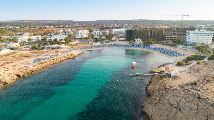 Aerial bird's eye view of Vathia Gonia beach, Ayia Napa, Famagusta, Cyprus. The landmark tourist attraction rocky bay at sunrise with golden sand, sunbeds, sea restaurants in Agia Napa, from above.
