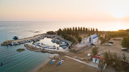 Aerial bird's eye view of coastline sunset, landmark white washed chapel Agia Triada beach, Protaras, Famagusta, Cyprus from above. Tourist attraction Ayia Trias bay church, sand, port at sunrise.