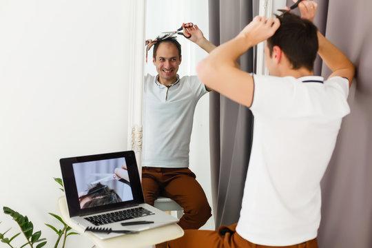 coronavirus mens haircut at home, online hairdressing tutoring on a laptop