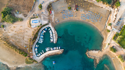 Aerial bird's eye view of coastline chapel, Agia Triada beach, Protaras, Famagusta, Cyprus from above. Tourist attraction Ayia Trias bay church, fishing village port with boats, sunbeds at sunrise.