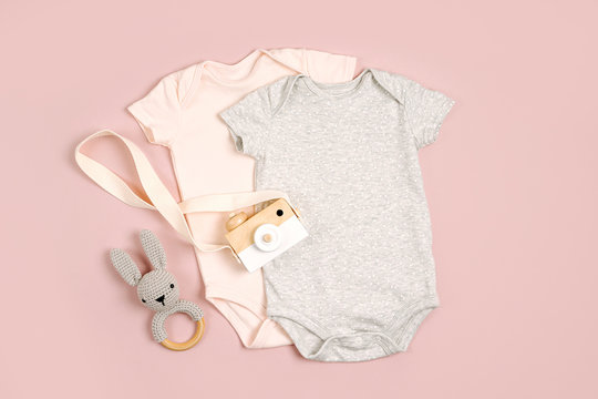 Cute baby bodysuits with toys. Set of kids clothes and accessories. Fashion newborn. Flat lay, top view