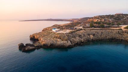 Aerial bird's eye view of coastline sunset, landmark white washed chapel Agioi Anargyroi, Cavo Greco Protaras, Famagusta, Cyprus from above. Ayioi Anargiroi church, rock cliff sea caves at sunrise.