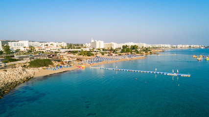 Aerial bird's eye view of Fig tree bay in Protaras, Paralimni, Famagusta, Cyprus. Famous tourist attraction golden sand family beach with boats, sunbeds, water sports pier, swimming in sea from above.