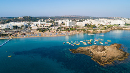 Aerial bird's eye view of Fig tree bay in Protaras, Paralimni, Famagusta, Cyprus. Tourist attraction golden sandy beach with boats, sunbeds, sea restaurants, water sports on summer holidays from above