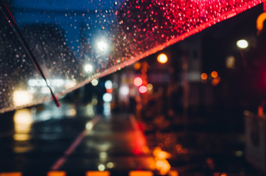 Close-up Of Wet Illuminated Road In City At Night