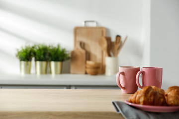 Wall Mural - Wooden table in a sunny kitchen in the morning light during breakfast