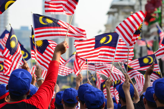 Rear View Of People Waving Malaysian Flags In City