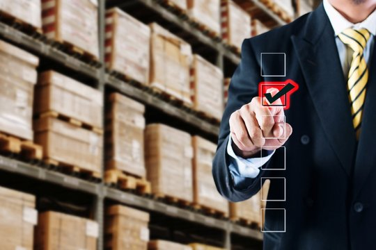 Digital Composite Image Of Businessman Touching Check Mark Against Crates On Shelves