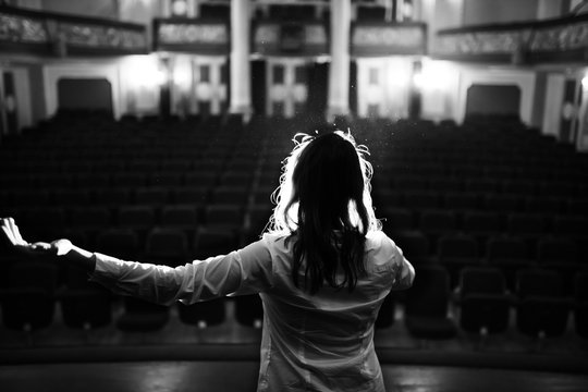 Entertainer performing on a stage in a empty theater,concert hall without fans.No audience.COVID-19 canceled show.Opera house without spectators.Playing to empty seats.Actor/singer entertaining no one