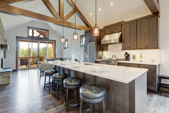 Amazing modern and rustic luxury kitchen with vaulted ceiling and wooden beams, long island with white quarts countertop.