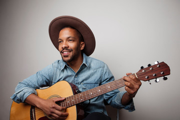 Portrait of happy bearded black man playing guitar isolated on white background. Fotomurales