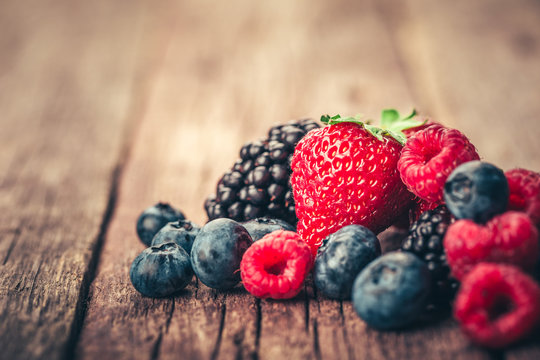 Fresh Summer Berries mix with Strawberry, Raspberry, Red currant, Blueberry and Blackberry on wood background.
