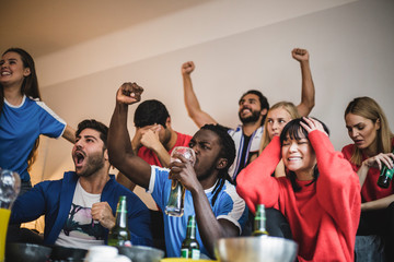 Multi-ethnic friends watching soccer match while sitting against wall at home