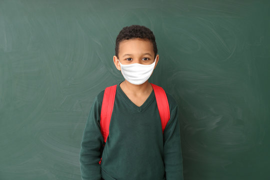 Cute African-American schoolboy wearing protective mask in classroom. Concept of epidemic