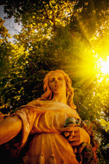 Wall Mural - Bottom view of ancientstone statue of wonderful angel in the rays of the sun. Selective focus.