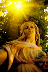 Wall Mural - Bottom view of ancient stone statue of wonderful angel in the rays of the sun.