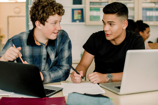 Male students talking while sitting by table in classroom