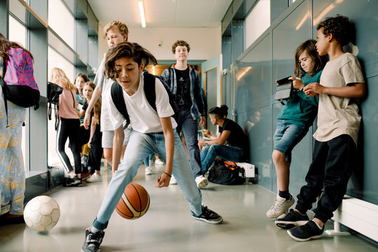 Boy playing with basketball during lunch break in school corridor