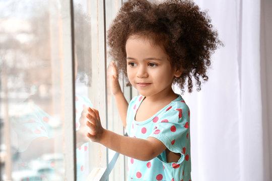 Little African-American girl near window. Child in danger