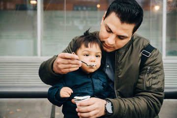 Father feeding baby food to son while sitting on bench in city