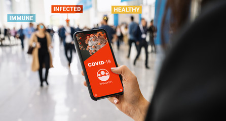 coronavirus tracking app on a mobile smartphone. Close up of woman tracking crowd of people in a smartphone screen application. Hand holding smart device. Mockup website. covid-19 corona virus tracker Fototapete