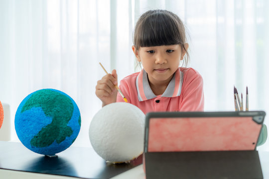 Asian elementary schoolgirl painting the moon in science class learning about the solar system via video conference with teacher and other classmates at home, Homeschooling and distance learning..